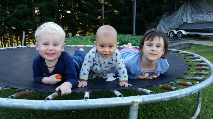3 young children smiling as they all look ahead laying on a trampoline