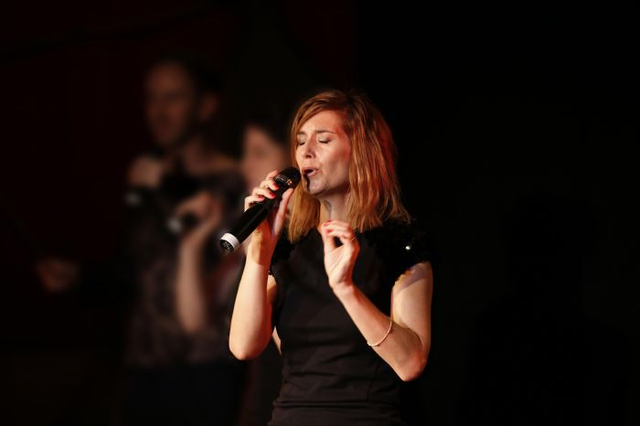 Woman holding a microphone and singing, with eyes closed