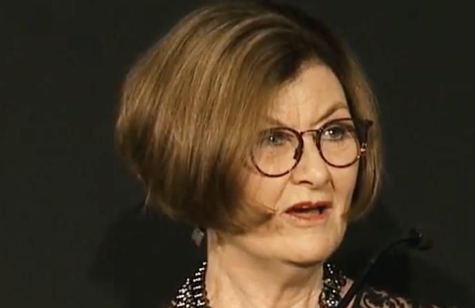 Headshot of woman with glasses with head turned slightly to the side mid way in speech, looking annoyed